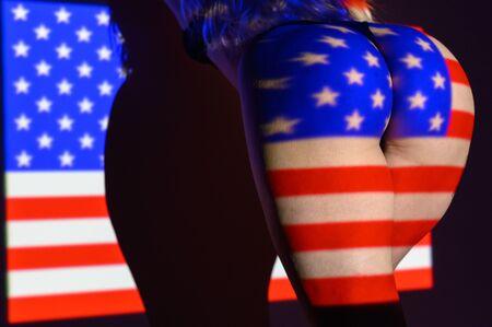 Die Projektion der Flagge der Vereinigten Staaten von Amerika auf einen schönen großen weiblichen Arsch. Der Projektor glänzt mit einer Fahne auf einem weiblichen Körper.
