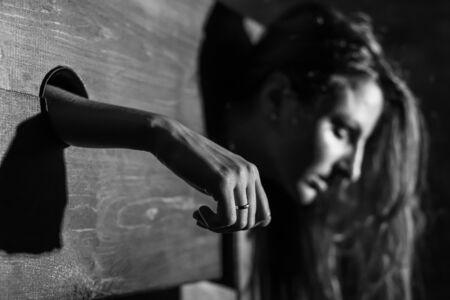 Una donna dai capelli rossi è imprigionata in una gogna di legno durante i giochi. BDSM Fantasie erotiche.Subordinazione. Giocattoli per adulti. incolore. Archivio Fotografico