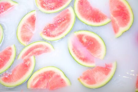 Turbid soapy water in bath with slices of watermelon. top view in full frame. The largest berry. spa with milk in the bath for rejuvenation