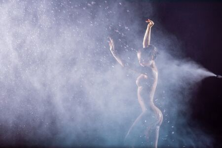 A beautiful European nude woman stands under the jets of water in the dark. Flashes lighting a girl without clothes in drops of water. A delightful slim figure. Stock fotó