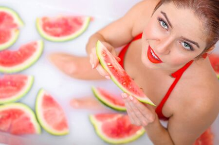 Portrait of a woman in a red swimsuit eating a watermelon and smirking. Redhead girl with red lipstick takes a bath with milk and fruit to rejuvenate her skin. Body care.