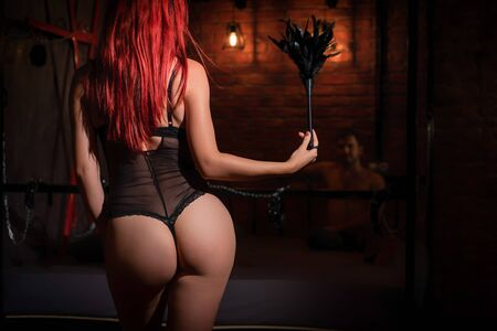 A redhead woman with a beautiful booty in black underwear stands with a whip and dominates the man during sexual games. BDSM Erotic fantasies. Subordination. Toys for adults. Stock Photo