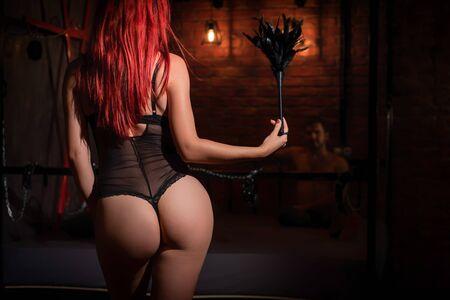 Eine rothaarige Frau mit einem schönen Hintern in schwarzer Unterwäsche steht mit einer Peitsche und dominiert den Mann beim Spielen. BDSM Erotische Fantasien. Unterordnung. Spielzeug für Erwachsene.
