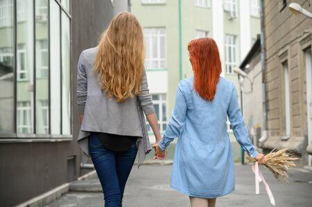 Paseo. Dos amigas caminan por la calle cogidos de la mano. Las espaldas de dos hermosas mujeres en un paseo con un ramo de flores secas. cosas arrugadas.