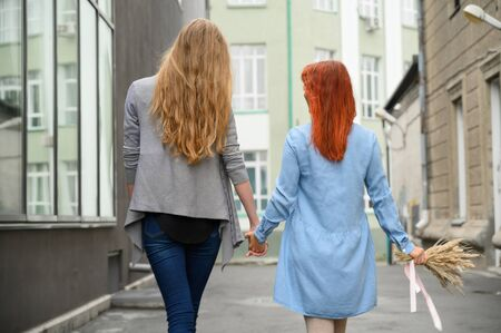 Stroll. Two girlfriends are walking along the street holding hands. The backs of two beautiful women on a walk with a bouquet of dried flowers. crumpled things.