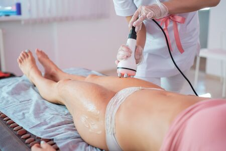 Woman receives an electric massage against cellulite. The doctor performs ultrasonic cavitation correction of the body contours for the patient. Anti-cellulite procedure on the hips in the spa