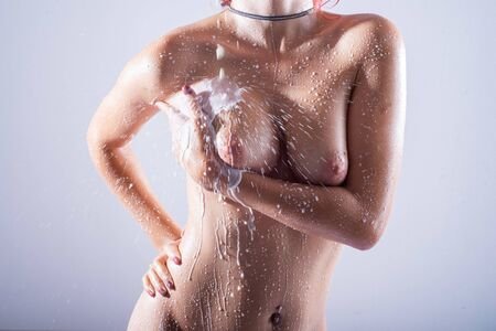 Close-up of a naked female breast with drops of milk. White water flows down the mammary glands of a beautiful girl. Gorgeous boobs in droplets. Wet nude woman with a beautiful figure.