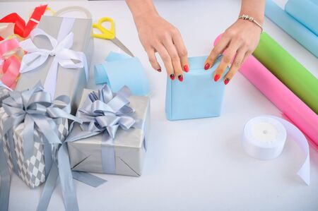 A woman wraps Christmas presents in wrapping paper and ties a ribbon bow. Close-up of womans hands preparing surprises for the new year. Workflow of a derator. Desktop. Stock Photo