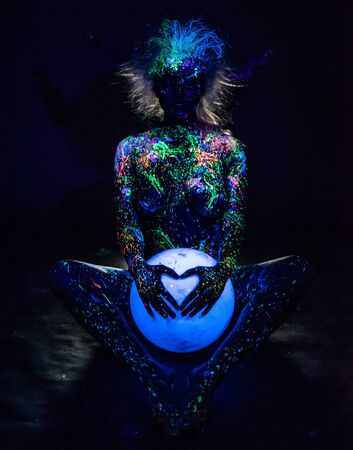 A woman painted with fluorescent powder holds a spherical lamp. Closeup of the legs of a girls hands with colored body spray. Round neon night light.