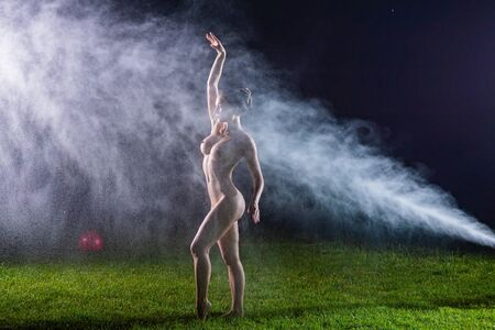 A beautiful European nude woman stands on a lawn under sprinkler at night. Flashes illuminate a girl without clothes in drops of water lawn splashes. Stock fotó