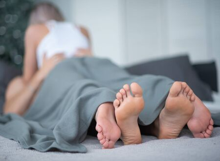 Close-up of male and female legs. The loving couple lies and embraces on the bed under a gray blanket. Light room. Reklamní fotografie