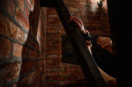 BDSM Nahaufnahme der Hände in Handschellen. Der Mann dominiert und bindet seine Herrin an das Andreev-Kreuz. Spiele für Erwachsene. Ziegelwand. Roter Raum.