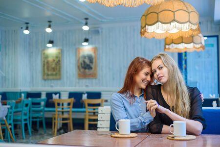 Gleichgeschlechtliche Beziehungen. Glückliches Paar, das in einem Café sitzt. Mädchen halten sanft Händchen und trinken Kaffee. Umarmung von liebenden Frauen. LGBT. Zwei beste Freunde im Café.