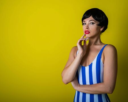 Beautiful young woman in a black short wig and a striped swimsuit posing on a yellow background. Attractive girl with sensual lips is flirting at the camera. Bright makeup.