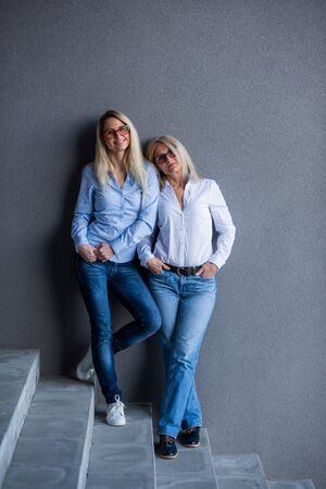 Portrait of two beautiful women of different generations against a gray wall. Family resemblance. Mother and daughter in a jeans shirt and glasses. Well-groomed elderly woman.