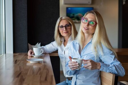 eautiful blonde with glasses and her elderly mother are sitting in a cafe and drinking coffee. Mothers Day. Beautiful aged woman and her adult daughter are smiling and chatting. Related resemblance. Stock fotó