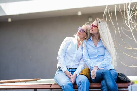 Two surprisingly similar women are sitting on a bench in an embrace and smiling. A middle-aged woman and her elderly mother. Beautiful well-groomed mother and daughter family look. Stock fotó