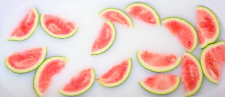 Turbid soapy water in bath with slices of watermelon. top view in full frame. The largest berry. spa with milk in the bath for rejuvenation..