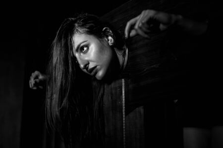 Una donna dai capelli rossi è imprigionata in una gogna di legno durante i giochi. BDSM Fantasie erotiche.Subordinazione. Giocattoli per adulti. Archivio Fotografico