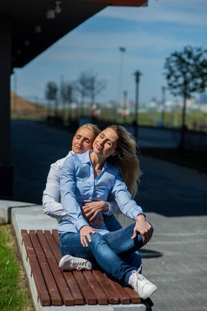 Two surprisingly similar women are sitting on a bench in an embrace and smiling. A middle-aged woman and her elderly mother. Beautiful well-groomed mother and daughter family look. Фото со стока