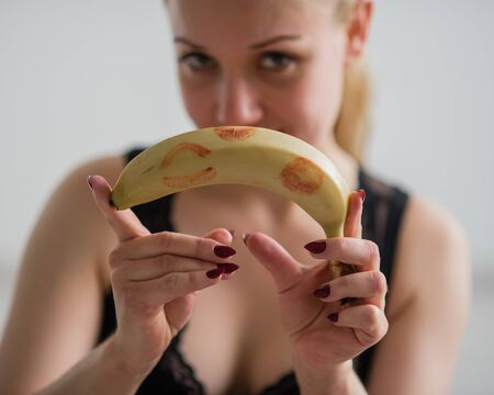 Blonde holds an unpeeled banana with red lipstick marks. The concept of oral sex. Seductive look. Appetizing fruit. Stock Photo