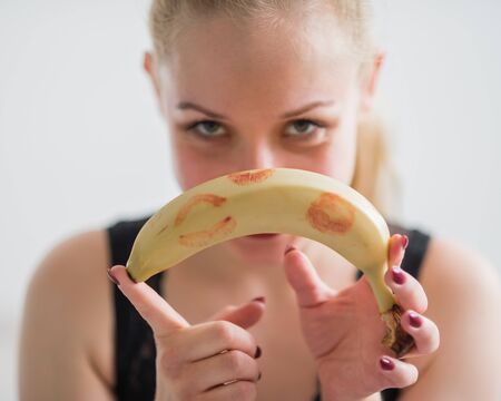 Blonde holds an unpeeled banana with red lipstick marks. The concept of oral sex. Seductive look. Appetizing fruit.