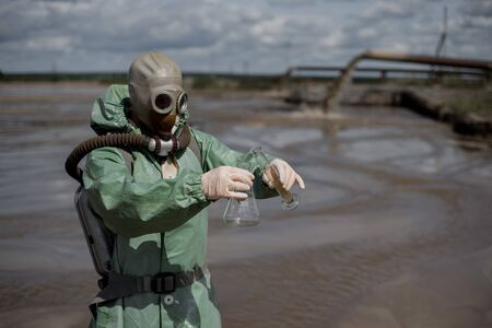 A scientist takes a sample of water from a reservoir after the release of chemical waste. A man in a respirator and a green protective suit from radiation. Water analysis experts. Mask.