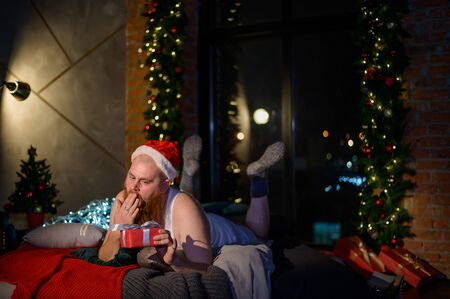 Humor on the subject of Christmas. A nerd with a red haired girl in a Santa Claus hat lies on a bed and uncovers a gift. Santa received a gift. Stock Photo