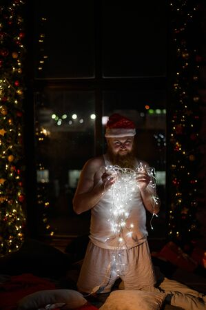 A comic image of santa claus in underwear on christmas eve. A man in a suit of Santa Claus holds a garland with lights in the New Year. A parody of a female photo shoot. Stock Photo