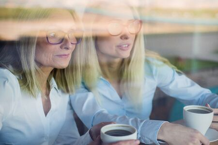 Two friends are enjoying coffee in a coffee shop, looking through a glass with reflections, sitting at a table chatting. Elderly Mother and adult daughter in a cafe. Mothers Day. Family resemblance. Stock Photo