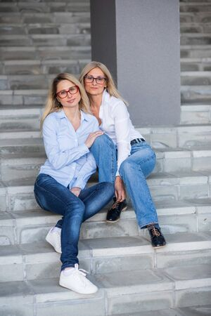 A beautiful blonde with glasses and her mature mother are sitting on the stairs outdoor. A well-groomed elderly woman hugs her adult daughter tightly. Love and family values. Mothers Day.