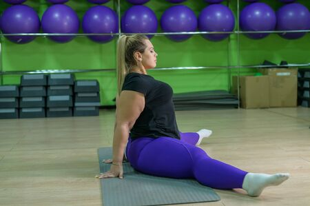 A fat woman is engaged in fitness in the gym. A girl with a lot of overweight trying to lose weight with the help of sports, does stretching exercises.