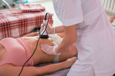 procedure removing cellulite on female abdomen, cavitation belly massage. Ultrasonic massage for weight loss. Correction of a female figure without surgical intervention. Close-up of the tummy. Stock Photo