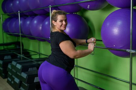 A fat woman is engaged in aerobics and trying to lose weight. An obese girl is relaxing in the gym with fitness balls. Stock Photo