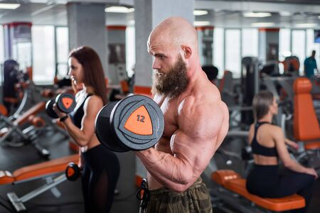 A bearded man and a group of women are engaged in the gym with dumbbells. The bodybuilder does exercises for biceps and triceps. A lesson from a personal trainer. Stock Photo