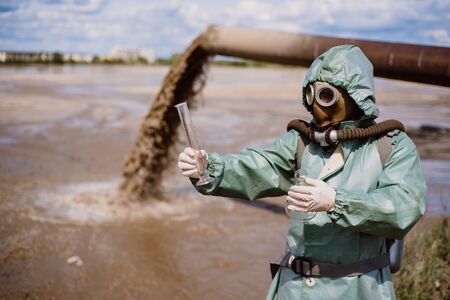 A male environmentalist in a protective suit and gas mask takes a sample of water. Scientist doing toxicological study. Banque d'images