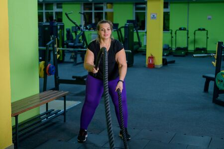 Fat woman doing strength training using battle ropes in the gym. An obese athlete moves the ropes in a wave motion to train fat burning. Stock Photo