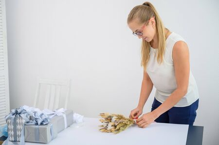 The blonde in glasses and a white blouse collects a bouquet of dried flowers and cotton in a white studio. A charming florist smiles at work.