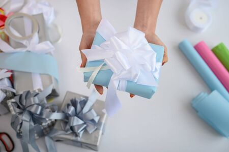 Close-up of female hands wrapping gifts for the new year. Woman holds handmade christmas gift. Preparation for the holiday. Box with a bow. Desktop with wrapping paper.