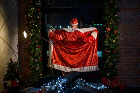 Humorous image of a man in a suit of Santa Claus showing striptease at the window. Bad Santa Claus opened his suit for a joke. Vulgar humor Stock Photo