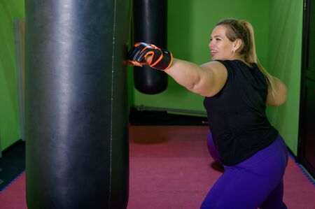 A fat woman is training kickboxing in the gym. A girl in boxing gloves beats a punching bag. Stockfoto