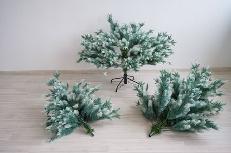Close-up of pieces of artificial Christmas tree against a white wall. The process of mounting and decorating a tree for the new year. Compound reusable spruce. Decoration for the holiday. Stock Photo