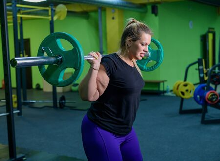 Overweight woman crouches with a barbell in the gym. A fat girl does exercises on the buttocks. Goes in for sports for weight loss.