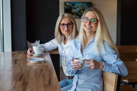 eautiful blonde with glasses and her elderly mother are sitting in a cafe and drinking coffee. Mothers Day. Beautiful aged woman and her adult daughter are smiling and chatting. Related resemblance. Stock Photo