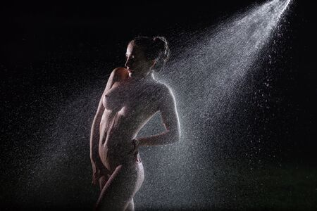 A beautiful European nude woman with silicone breasts stands at night under a sprinkler. Flashes illuminate the girl without clothes, in drops of spray. Shower dripping on a female body in the dark Stock Photo