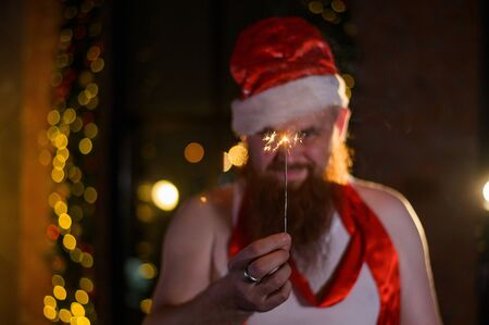 Santa with Christmas sparkles on holiday. A man with a red beard in a Santa Claus hat is celebrating the New Year. Happy New Year and Christmas. Stock Photo
