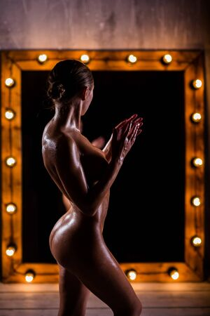 Slender sexy Nude girl in oil posing in front of the mirror. Very a beautiful figure, the beautiful thumping, narrow waist, luster of on the skin.