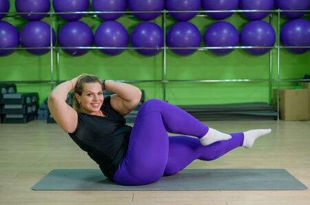 A fat woman is engaged in fitness in the gym. A girl with a lot of overweight trying to lose weight with the help of sports, does exercises for abdominal muscles.