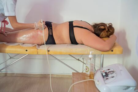 A fat woman lies on her couch with her stomach and receives a thigh massage. The procedure for weight loss.