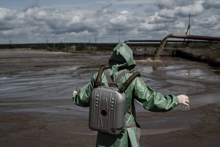 A male environmentalist in a green protective suit and gas mask takes a sample of water in a polluted lake. Waste from production. A scientist does a toxicological study of toxic waste. Banque d'images - 133727800